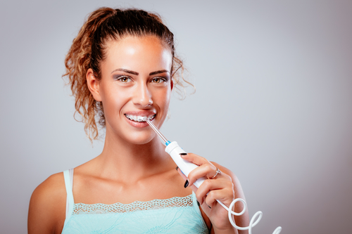 woman using water flosser to clean teeth