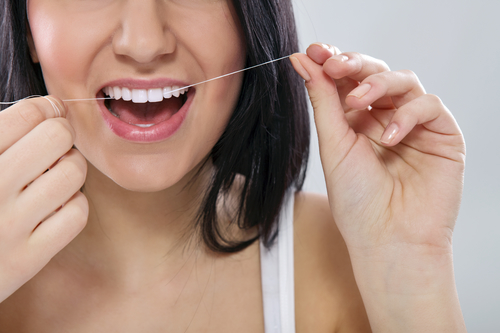 Woman flossing all on four implant