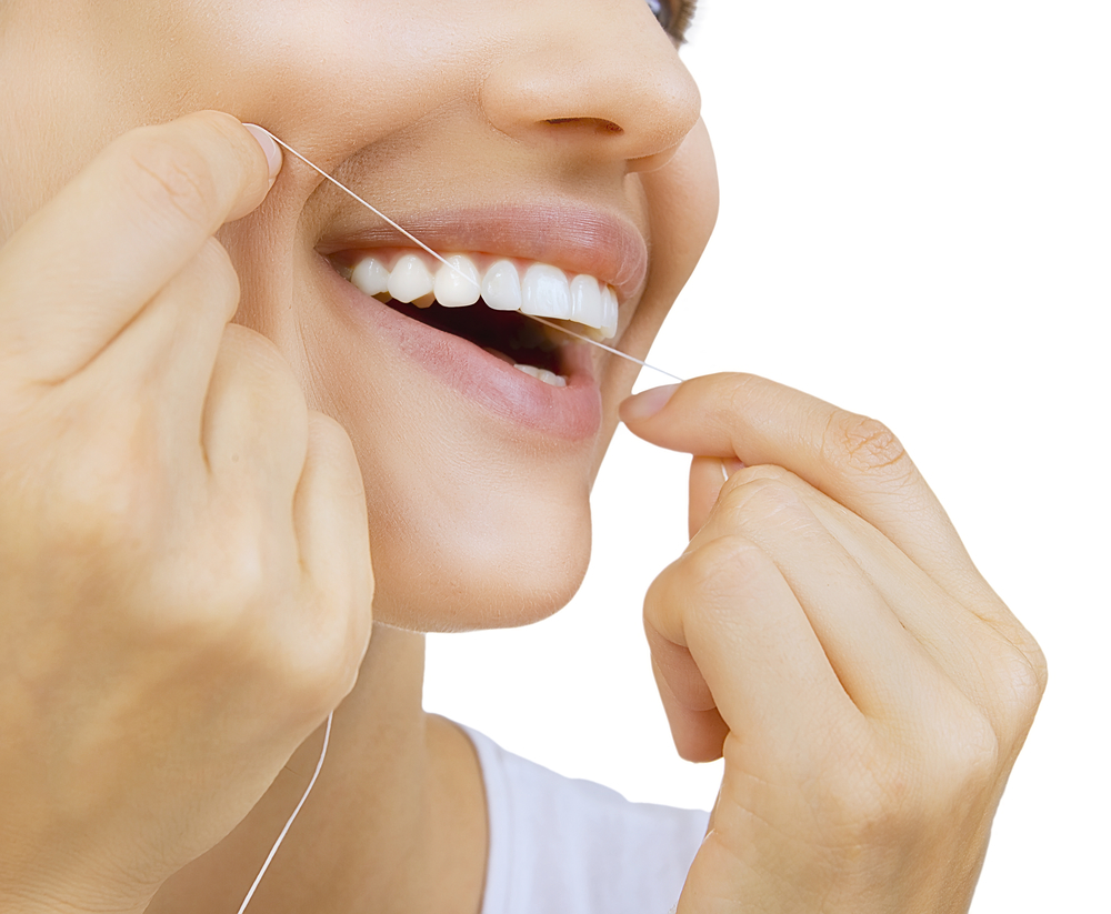woman flossing dental crown
